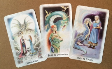 The 2 of Cups, 4 of Pentacles & Page of Wands from The Celtic Dragon Tarot by Lisa Hunt.
