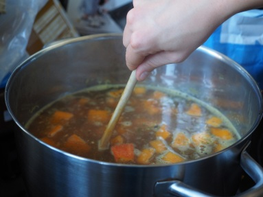 A wooden spoon stirring a pot of vegetables on the stove.